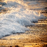 Прибой, пенные волны с шорохом набегают на берег