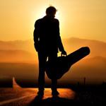 Силуэт мужчины с футляром для гитары на фоне заходящего с...
