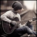 Парень сидит на рельсах и играет на гитаре